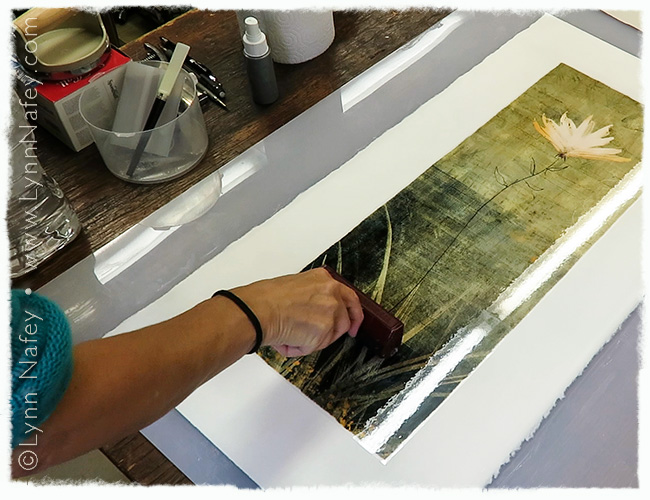 """Using a brayer to press the image of """"Rising"""" onto the paper"""